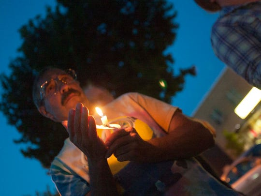 About 125 people lit candles and sang songs Friday night at a candlelight vigil in Sheboygan following violent protests a week earlier in Virginia.