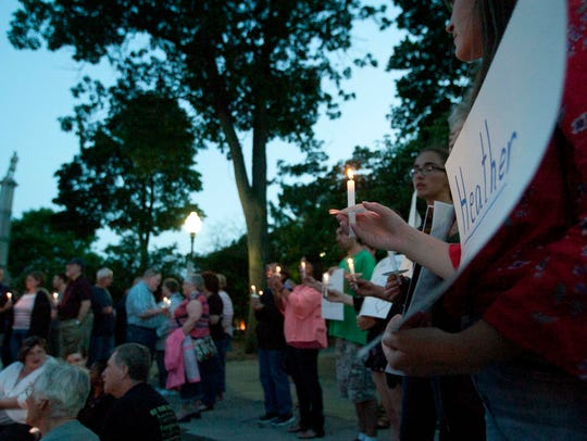 About 125 people lit candles and sang songs Friday