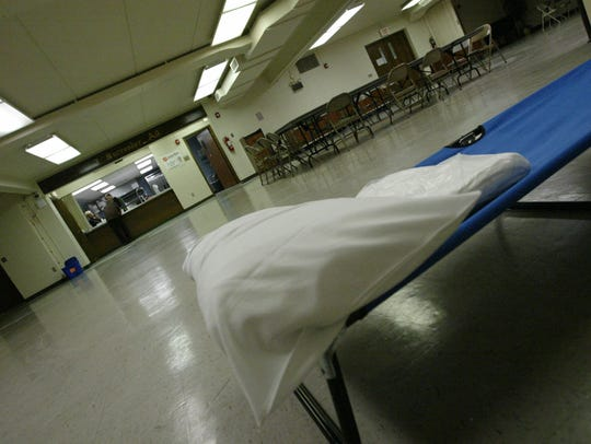Volunteers set out a cot earlier this month inside the basement of the Sheboygan Salvation Army, where homeless can find shelter during January.