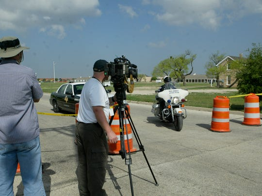 Media stand outside the barricades as San Angelo police officers and DPS troopers guard Fort Concho National Historic Landmark in April 2008.