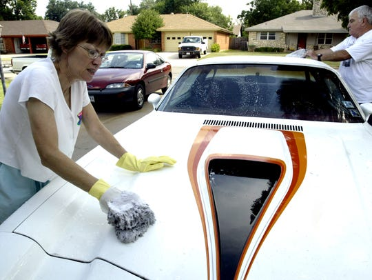 Betty Taylor, left, washes the dirt off her 1972 Camaro as her husband, George Taylor, helps prepare for their July 2005 drag race to celebrate their 40th anniversary.