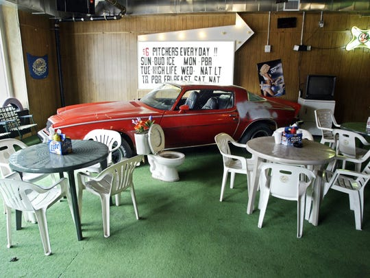 """The interior of Paradise Park restaurant and bar features a """"trailer park"""" atmosphere complete with AstroTurf floor covering and toilets converted to planters."""