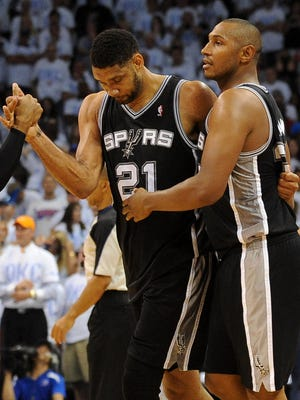 Spurs star Tim Duncan gets a high-five from guard Patty Mills while leaving the court with forward Boris Diaw after Game 6 vs. the Thunder.