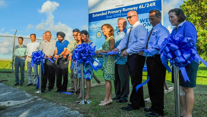 "Charles ""Chuck"" Ada, , third from right, Guam Airport Authority executive manager, and others cut through a ribbon cutting during a brief ceremony at Tiyan on Monday, July 27. The ribbon cutting was held to celebrate the official opening of the extended runway ""6L/24R"" at the A.B. Won Pat International Airport. Work, at the cost of more than $70 million, included extending the original runway length by 1,000 linear feet at opposite ends, the replacement of existing electrical wiring, the installation of wiring for the additional length and the installation of a new Instrument Landing System for the full length of the extended runway, according to an airport brochure."