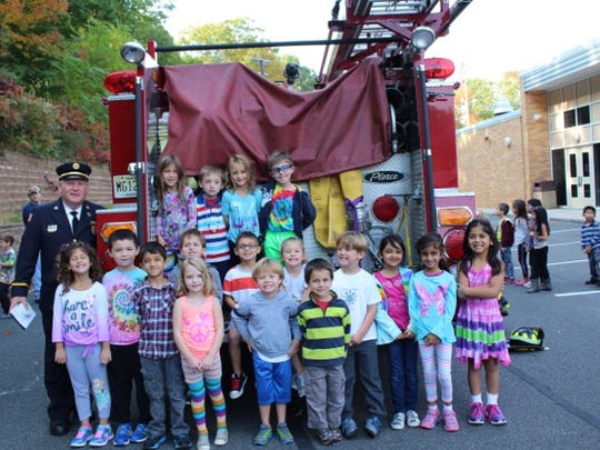 Watchung Fire Marshall, Gary Greves, assists Mrs. Miller's kindergarten class with helping to celebrate Fire Prevention Week at Bayberry School