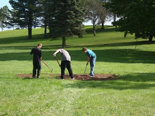 Manitowoc Lincoln High School students help move dirt as part of efforts at Manitowoc's Red Arrow Park.