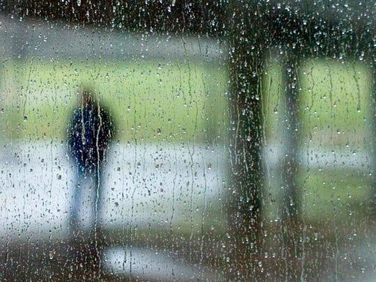 FILE - Rain falls across a window a the Civic Coliseum