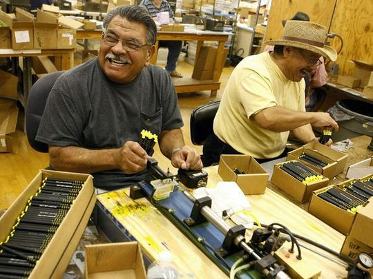 Frank Rodriguez (left) and Paul Valdez fill highlighters with ink at the West Texas Lighthouse for the Blind in San Angelo.
