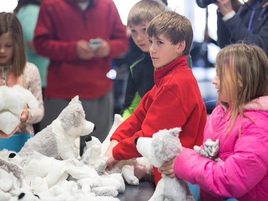 "Kids participate in a stuff-a-wold activity during an open house held Saturday at Moraine Park Technical College. Kids enjoying ""stuff a wolf"" activity. Maximus the wolf is the school mascot."