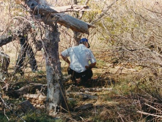 A Tom Green County Sheriff's investigator examines remains found in the southeast portion of the south pool of Twin Buttes Reservoir. Hunters found remains, later identified as teenagers Shane Stewart and Sally McNelly, about four months after the two went missing in 1988.