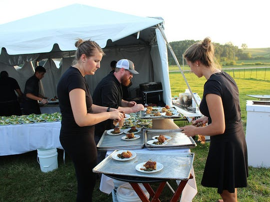Staff serves up pork liver and brick cheese stuffed doughnuts alongside a whiskey cranberry gravy during the Farm to Table event on Aug. 19.