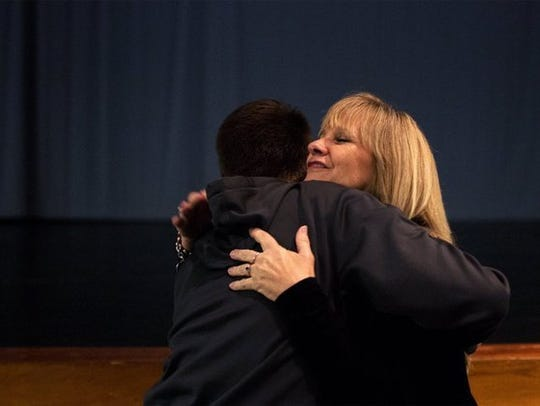 Renee Napier hugs a student after a speaking presentation