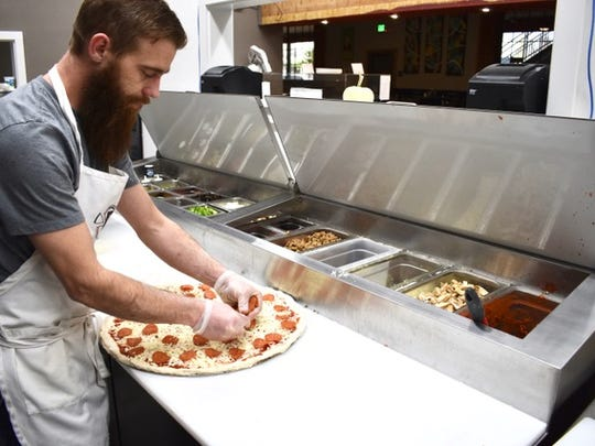 Co-owner Brandon Smith makes a pizza at Fratelli's on California Street.