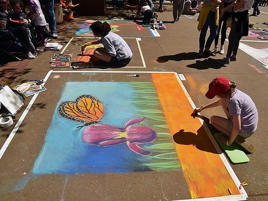 Avery Burgess works on her chalk art project at the