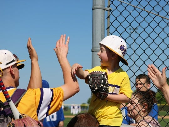 Michael Grzankowski high fives South Amboy players at a game
