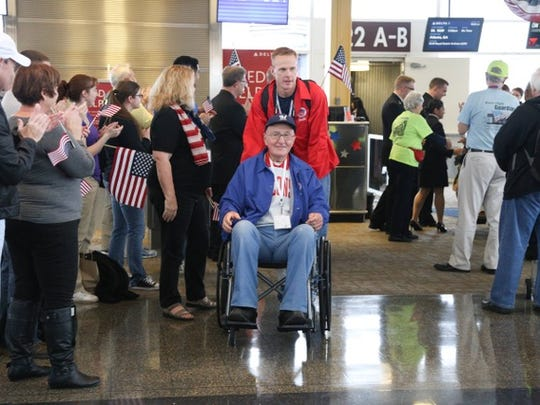 Lee Roy Wagner and his guardian Doug Johnsen are greeted by cheering crowds at Reagan Airport in Washington, D.C., during a November 2015 Stars and Stripes Honor Flight.