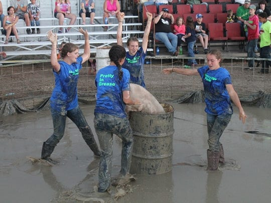 A team participates in the pig wrestling event during the 2014 Blaine County Fair.