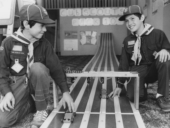 Cub Scouts Kirk (left) and Anthony Staresieic of Pack 103 demonstrate how Pinewood Derby race cars work during the Community Day at Devington Shopping Center in 1979.