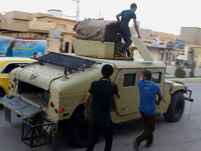 Teenagers ride on an armored vehicle belonging to the Iraqi army in Tikrit on June 11. Al-Qaida-inspired militants seized effective control Wednesday of Saddam Hussein's hometown of Tikrit, expanding their offensive closer to the Iraqi capital as soldiers and security forces abandoned their posts following clashes with the insurgents.