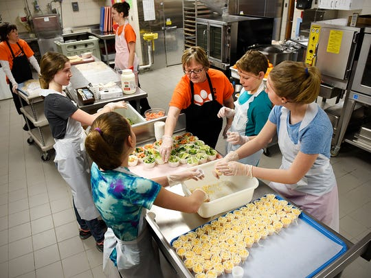 Head cook Judy Hommerding, center, works with students on Feb. 11 getting ready to serve lunch at Clearview Elementary School in Clear Lake.