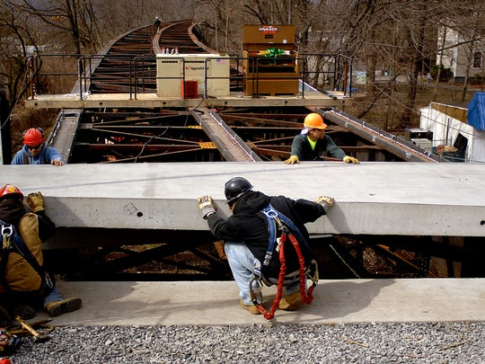 Employees with Harrison and Burrows Bridge Constructors Inc., located in Glenmont, N.Y., lower a 16-ton concrete pad onto the deck of the 1.25-mile-long Poughkeepsie Railroad Bridge at the east end of the project over Washington St. in Poughkeepsie. This pad is one of 974 to be placed on the bridge's deck during the Walkway Over the Hudson project.