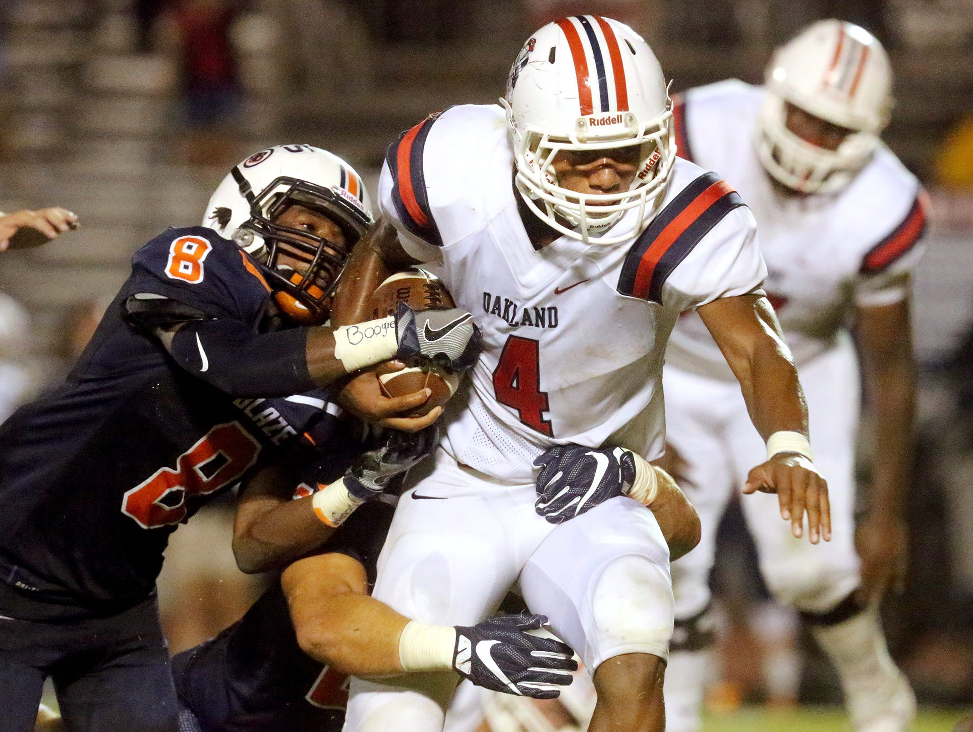Oakland's Lazarius Patterson (4) runs the ball as Blackman's Jamis Carson (8) and Anthony Ochoa (22) tackle Patterson during the game on Friday, Sept. 16, 2016, at Blackman.