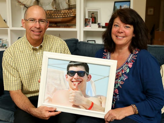 FILE PHOTO – Jeff and Lee Moniz hold a photo of their late son Tyler at their Bainbridge Island home.