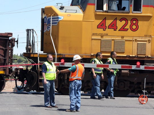 Police and others stand at the railroad crossing at San Marcial Street following a pedestrian-train accident Sunday.
