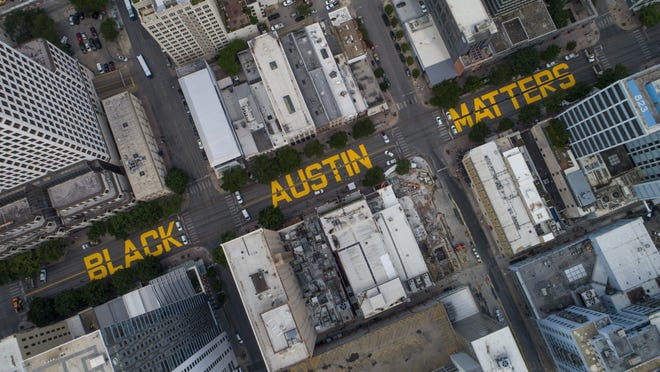 """""""Black Austin Matters"""" appears in large letters painted Tuesday on Congress Avenue. Capitol View Arts and the Austin Justice Coalition partnered with the city of Austin to make the statement against racism and police brutality."""
