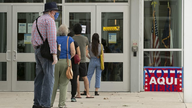 People wait in line to vote early at the Austin Independent School District Performing Arts Center on July 8.