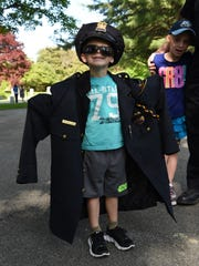 Dylan Holland, 4, wears part of his dad's uniform at a memorial in Poughkeepsie Rural Cemetery honoring those who have served in the Town of Poughkeepsie Police Dept. Dylan's grandfather also served for 30 years in the department.