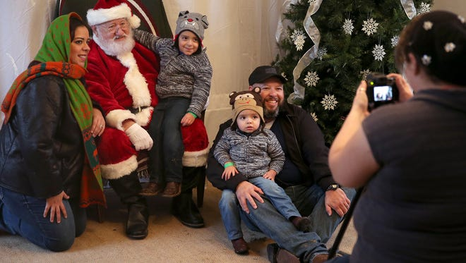 A family has pictures taken with Santa Claus during Christmas at Old Fort Concho.