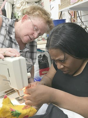 Rasheeda Wallace, right, practices techniques at SewGreen, a nonprofit on Arnett Boulevard that is run by a St. Stephen's deacon.