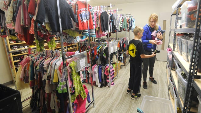 Joy Moudy and her son Graham sort through toddler clothing donations at the new headquarters of the Christian Service Center, which re-opened today at their new location at 3185 N 10th Street. The building was the former Woodlawn Church of Christ, which will continue to share some of the space. Moudy's mother and grandmother have also volunteered at the center, making it four generations of volunteers from her family.