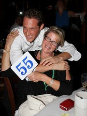Chef Brian Roland hugs guest Rose O'Dell King at the Rumrunners Celebrity Chef Night last year.
