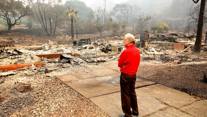 Mike Rippey looks over the burned out remains of his parents home at the Silverado Resort, Tuesday, Oct. 10, 2017, in Napa, Calif. Charles Rippey, 100 and his wife Sara, 98, died when wind whipped flames swept through the area Sunday night. (AP Photo/Rich Pedroncelli)