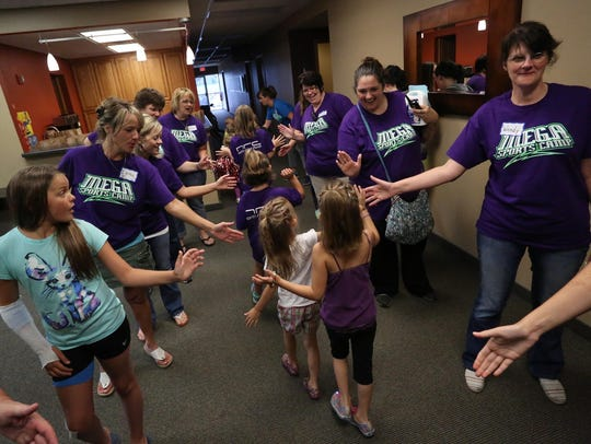 Girls get high-fives from volunteers as they head off