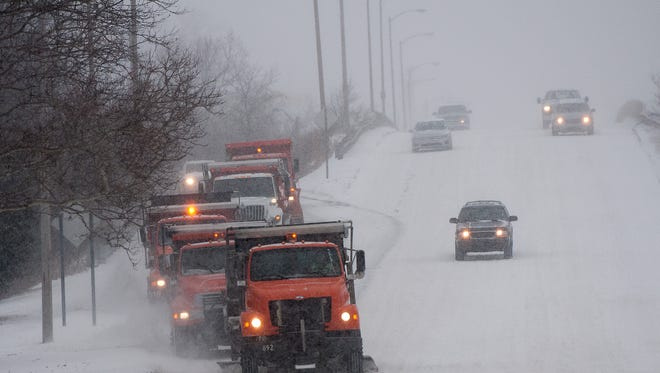 A line of City of Lansing snow plows and salt trucks make their way through the city streets Sunday morning in low visibility.