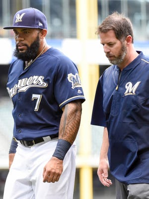 Eric Thames leaves the game with assistant athletic trainer Dave Yeager with an injury.