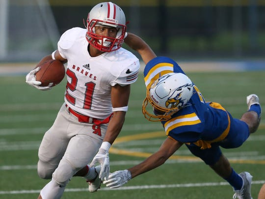 Canandaigua running back AJ Clifford runs away from the diving tackle attempt by Irondequoit's Isaiah Delario-Brown.