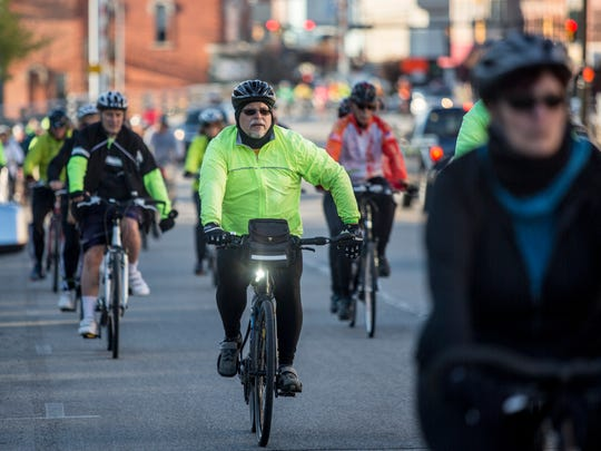 A cyclist communicates with other riders with a hand signal during the Ride of Silence Wednesday, May 18, 2016 on Military Street in Port Huron. The annual ride honors those that have been injured or killed in cycling accidents and aims to bring awareness to cycling rights and safety.