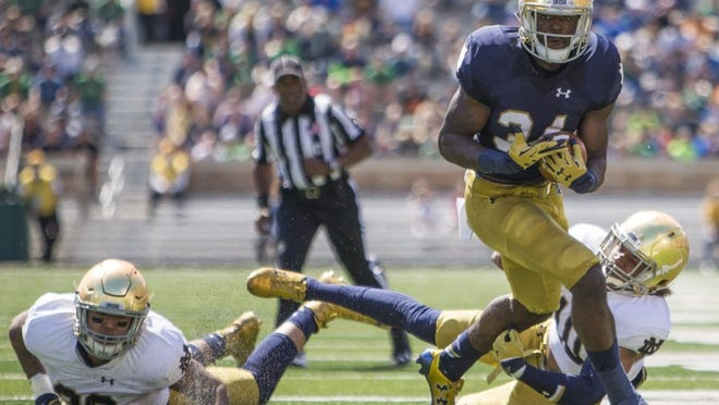 Robert Franklin / South Bend Tribune Notre Dame's Dexter Williams (34) breaks away from Josh Barajas (left) and Max Redfield on a touchdown run during the Blue-Gold spring game Saturday at Notre Dame Stadium in South Bend.