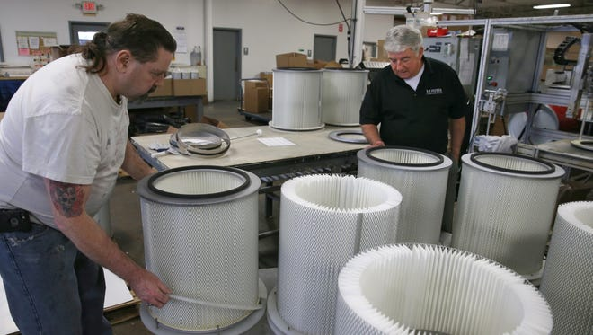 Steve Quinn, company president and co-owner, right, checks on a order of dust-collection filters being assembled by Henry Capron, left, at R.P. Feeder Corporation on Driving Park Avenue in Rochester Wednesday, May 11, 2016.