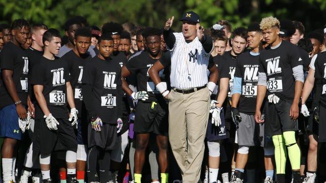 Michigan coach Jim Harbaugh, center, talks to athletes during Next Level Football Camp at Paramus Catholic High School, Wednesday, June 8, 2016, in Paramus, N.J. (AP Photo/Julio Cortez)