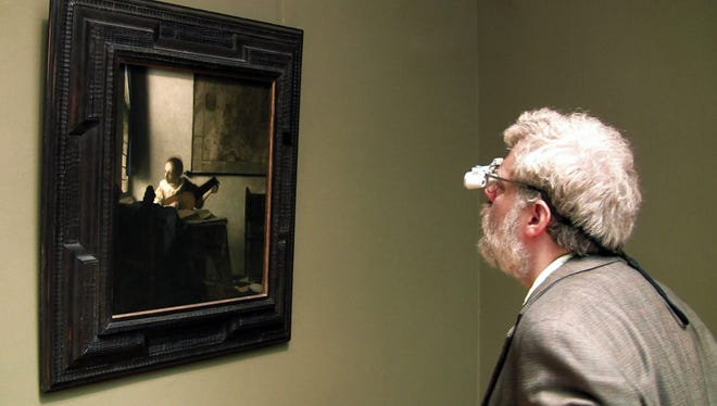 "Tim Jenison, wearing his surgical loupes, inspects Johannes Vermeer's ""Woman with a Lute"" at the Metropolitan Museum of Art in New York."