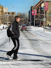 An IUPUI student walks across University Boulevard