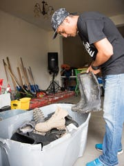 Pastor Bert looks for his rubber boots before heading out to perform hurricane relief work in Arecibo.