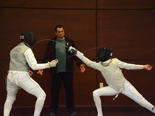 Instructor German Paz watches as two of his students fence. Students from the Naples Fencing Academy put on an exhibition for interested residents of the Arlington retirement community on Monday.
