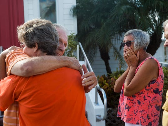 The Rev. Bob Wallace hugs Lisa Marteeny, as Connie Barker reacts to the news that Marteeny's husband, Lee, died the night before, outside of Everglades Community Church on Sunday, Sept. 17, 2017.
