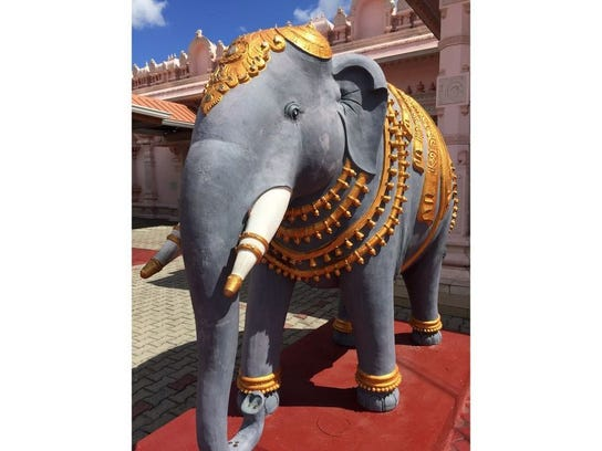 Outside the Dattatreya Temple in Trinidad, people leave coins in the elephant's trunk